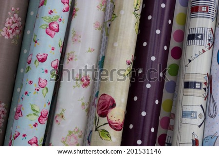 Rolls of oilcloth designs in a home interiors shop. - stock photo