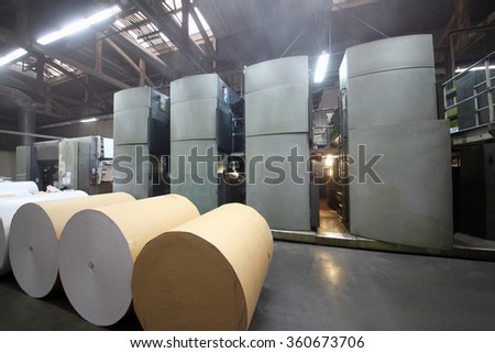 Rolls of paper and Roll 48-way offset printing machines in tipography - stock photo