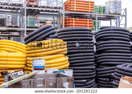 Rolls of plastic and rubber pipes or tubes stacked high in a warehouse or factory yard for use to supply utilities in construction and act as a conduit
