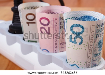 Rolls of polish currency money in electrical extension with connected plug, power board, concept of saving money on electricity, energy costs - stock photo