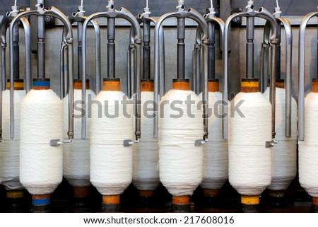 Rolls of spun cotton in a textile factory - stock photo