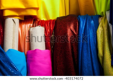 Rolls of textile, cloth and tissue of various colors on the market. Copy space.
