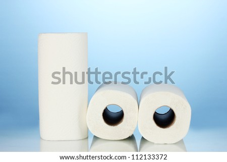 rolls of toilet paper on blue background - stock photo