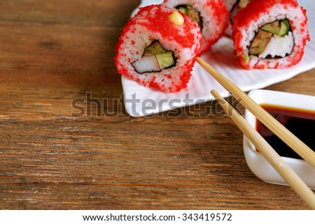 Rolls with sauce and sticks on wooden table close up - stock photo
