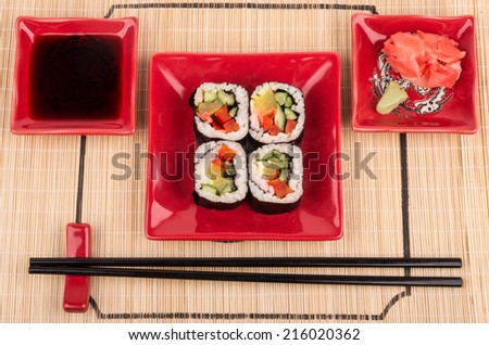 Rolls with vegetables on mat - stock photo