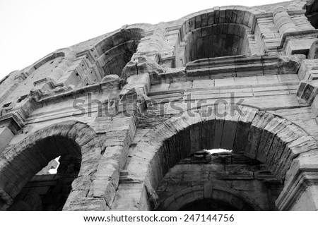 Roman amphitheatre in Arles (Bouches-du-Rhone, Provence-Alpes-Cote d'Azur, France) Aged photo. Black and white. - stock photo