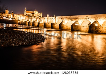 Roman Bridge on Guadalquivir river and The Great Mosque (Mezquita Cathedral) at twilight in the city of Cordoba, Andalusia, Spain. - stock photo