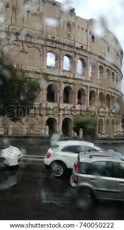 Roman Colosseum seen through a wet glass from a rain droplet of a car window on a cloudy day