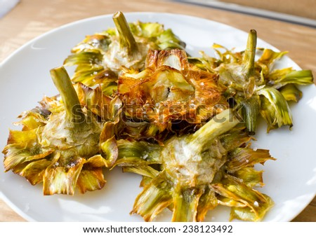 Roman fried artichokes (jewish style) with flakes of sea salt on a wooden table. - stock photo