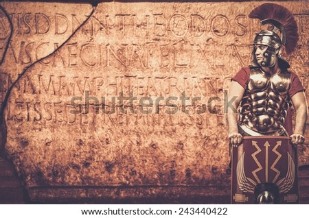 Roman legionary soldier in front of  wall with ancient writing  - stock photo