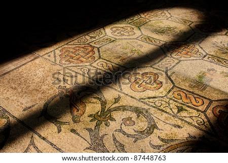 Roman mosaic in old church illuminated by church window - stock photo