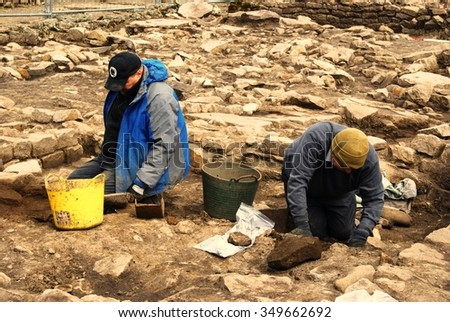 ROMAN SITE OF VINDOLANDA, UK - MAY 5 2013 Two unidentified archaeologists excavating ancient structures at the Roman Fortress and Settlement along Hadrian's Wall on May 5, 2012