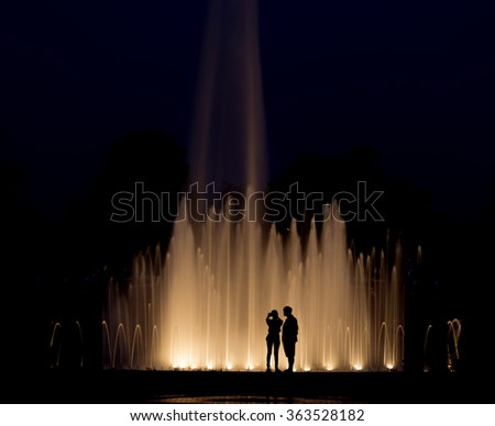 Romance abstract background, Couples take a photograph with fountain at night.