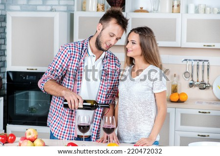 Romance in the kitchen. Attractive couple in love opens the wine in the kitchen while they cooking dinner. Man pours wine into a glass - stock photo