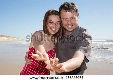 romance on vacation: couple in love on the beach flirting