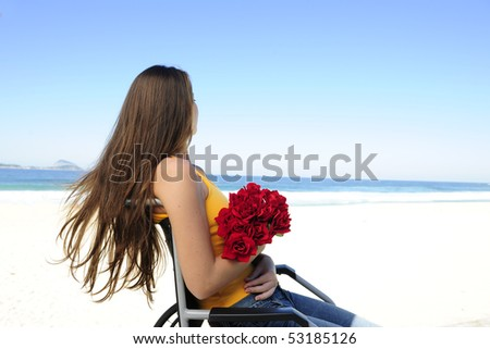 romance: woman in wheelchair with red roses - stock photo