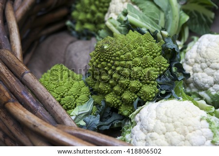 Romanesco cauliflower with its fractal shapes and Fibonacci sequences in focus,  and cabbage leaves in the background. - stock photo