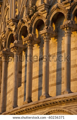 romanesque columns and arches at cathedral in Pisa Tuscany Italy in late afternoon golden light
