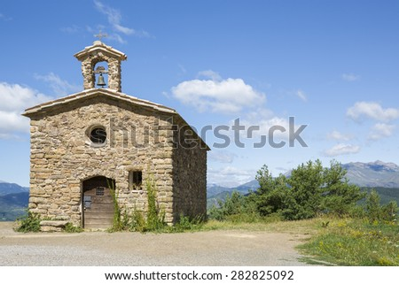 Romanesque hermitage of Sant Salvador de Irgo, Lleida (Spain) Background: sky, clouds, mountains and vegetation - stock photo