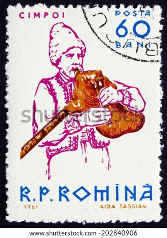ROMANIA - CIRCA 1961: a stamp printed in  Romania shows Peasant Playing Bagpipe, Musical Instrument, circa 1961 - stock photo