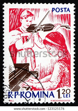ROMANIA - CIRCA 1962: a stamp printed in the Romania shows Girl at Piano, and Boy Playing Violin, circa 1962