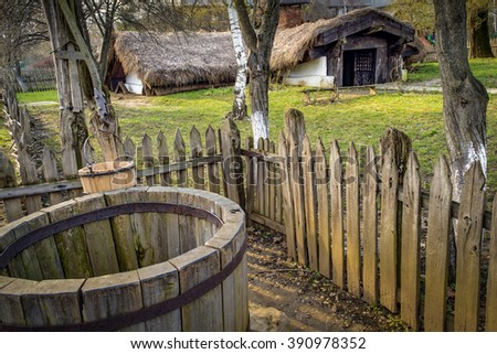 Romanian bordei is underground house similar to a cottage with a wooden fence and a water well in a rural environment with a rustic feel - stock photo