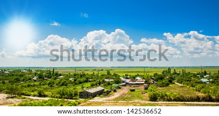 Romanian countryside landscape, village.Group of houses in the countryside. Sunny summer day and blue sky.old rural house.Romanian Farmland With Blue Sky and green meadows.Grassland and houses - stock photo
