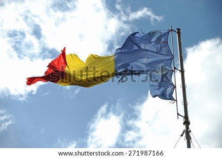 Romanian flag ripped of by the wind with blue sky on background - stock photo