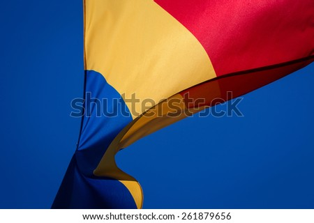 Romanian flag waving against blue sky. - stock photo