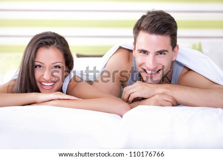 Romantic and cute young couple laughing in bed