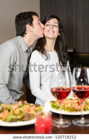 Romantic anniversary dinner. Young playful couple having fun during the celebration. Man kissing cheerful woman. Loving boyfriend and girlfriend - stock photo