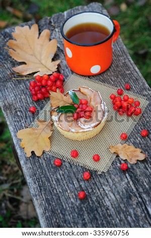 Romantic autumn still life with basket cake, cup of tea, rowan berries and leaves at wooden board - stock photo
