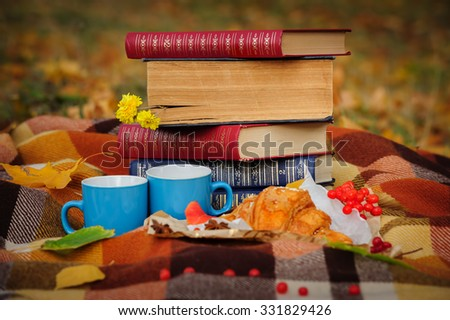 Romantic autumn still life with blanket, croissant, book, coffee cups and leaves, top view - stock photo