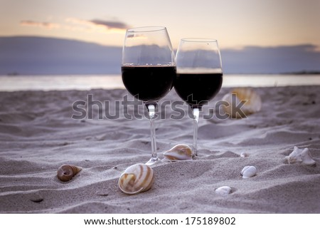 Romantic beach evening on the sunset: two glasses of wine, candles, shells, valentines day  - stock photo