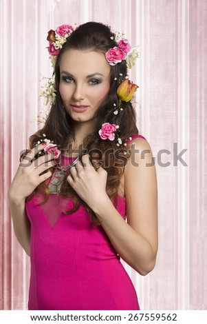 Romantic, beautiful, natural, brunette in pink dress. She has got hairstyle with spring flowers, dark make up, and nice necklace.  - stock photo