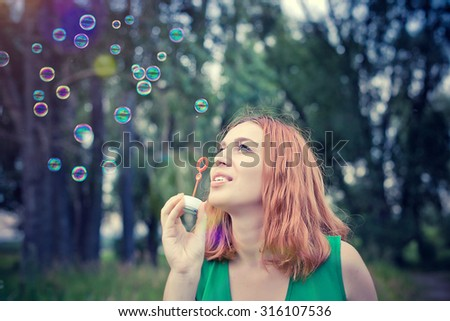 Romantic beautiful young smiles woman blowing soap balloons in a flower meadow - stock photo