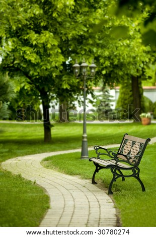 romantic bench in peaceful park in spring - stock photo