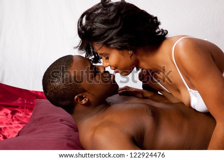 Romantic Black couple, he is reclining and she is leaning over him in her bra and kissing him as they embrace in foreplay - stock photo