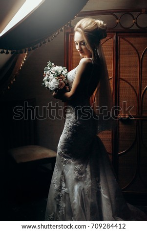 Romantic blonde bride in elegant white wedding dress with bouquet posing in luxury old room with wooden interior decorations, wedding morning preparation concept, sensual bride portrait