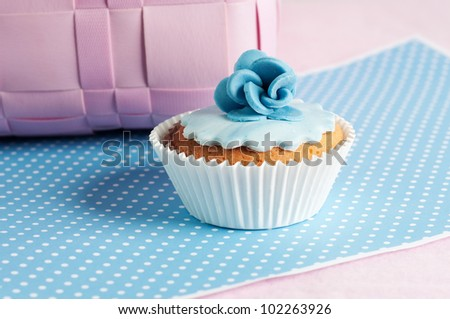 romantic blue flower cupcake in pink setting - stock photo