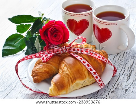 Romantic breakfast with tea in cups, croissants and rose - stock photo