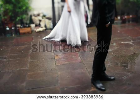Romantic bride & groom on old european street, feet closeup - stock photo