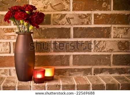 Romantic candle light and carnations in a vase against brick wall. Restaurant background concept with copy space to right. - stock photo