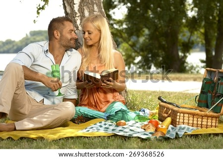 Romantic couple at marriage anniversary picnic. Casual blonde caucasian woman reading book and handsome man with glass. - stock photo