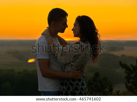 romantic couple at sunset on outdoor, beautiful landscape with bright yellow sky, love tenderness concept, young adult people