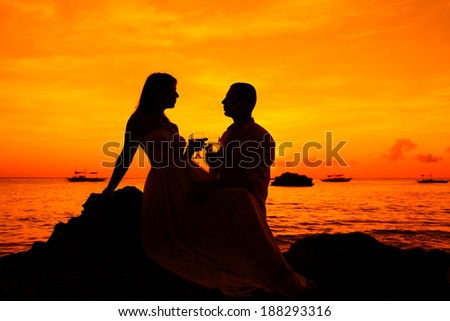 Romantic couple at tropical beach with sunset in the background - stock photo