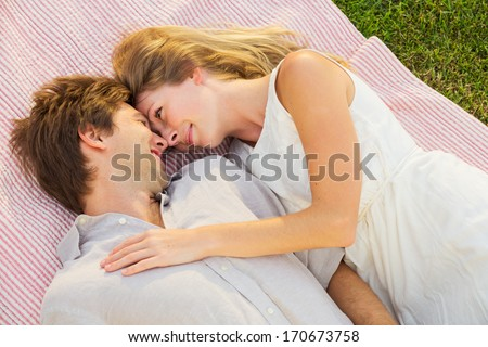 Romantic Couple Cuddling And Flirting In Park On Blanket
