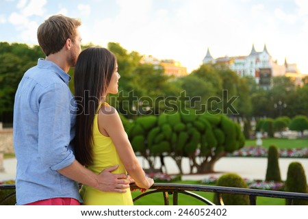 Romantic couple embracing in love enjoying view in park. Multicultural man and woman relaxing in el Retiro in Madrid, Spain, Europe. - stock photo