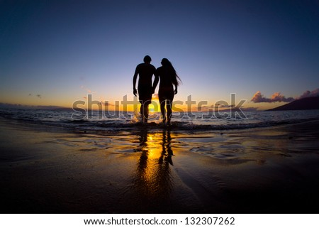 Romantic couple enjoying a beach walk at sunset - stock photo