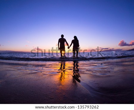 Romantic couple enjoying a beach walk at sunset - stock photo